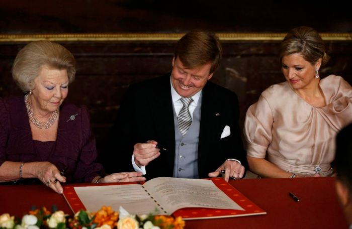 Queen Beatrix of the Netherlands passes the act of abdication to her son Crown Prince Willem-Alexander next to his wife Crown Princess Maxima during a ceremony at the Royal Palace in Amsterdam