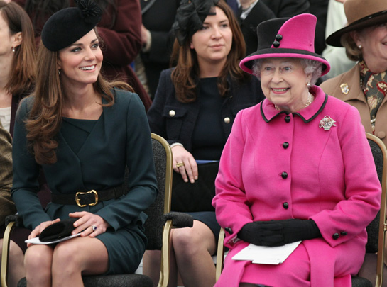 Rebecca is seated in black behind Kate and the Queen (via Hello!)